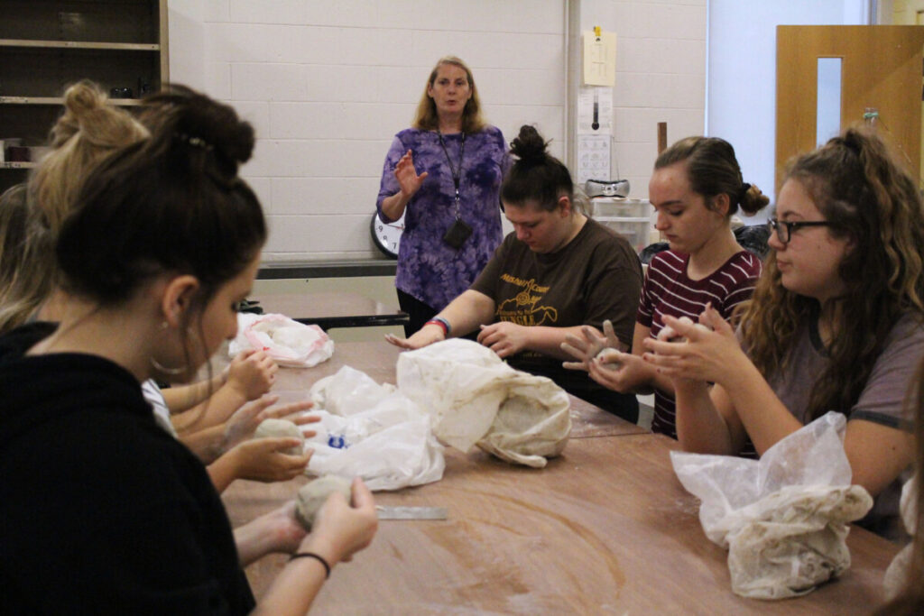 Students kneed clay to relieve stress.