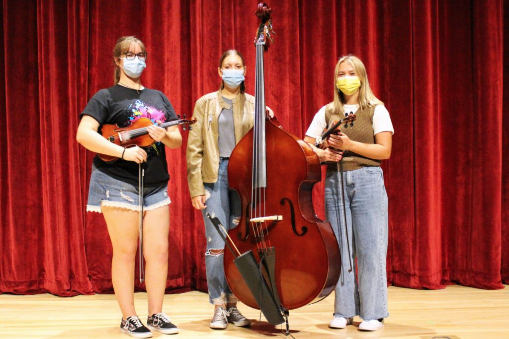 Pictured from left are John Marshall High School Strings students Megan Huff, Grace Gatts and Sofiah Bozenske, who are standing in front of a red curtain while holding their violins.