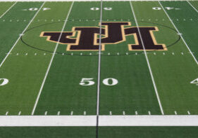 The JM football field turf is ready for this Friday's game. The 50 yard line JM logo is painted brown and gold.