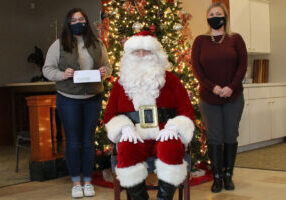 Alt txt: Pictured from left: WJMH Media teacher Carly McElhaney, Santa Claus and GKT Attorney Teena Miller in front of Christmas tree decorated with red bulbs and white lights.